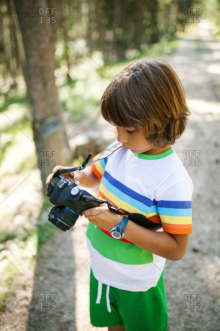 Young boy holding camera while walking in nature