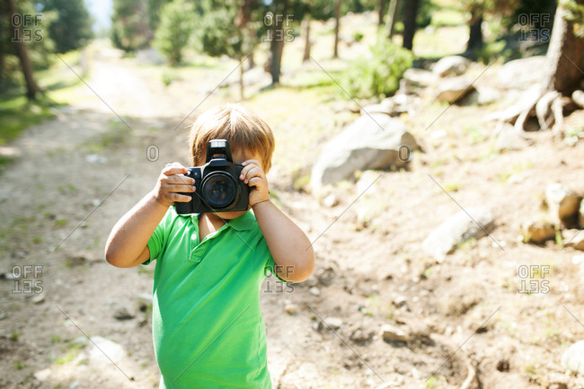 Little boy holding camera in nature