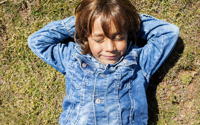 Boy lying in grass on a sunny day