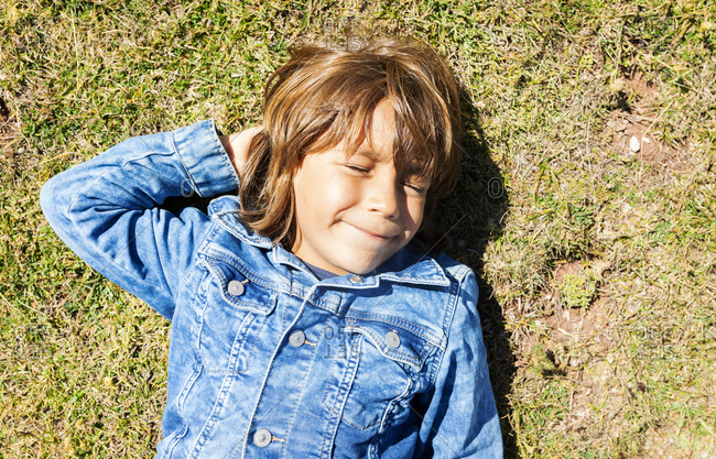 Portrait of boy lying in grass on a sunny day