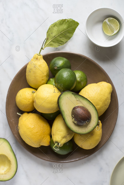 Avocado on a plate with limes and lemons