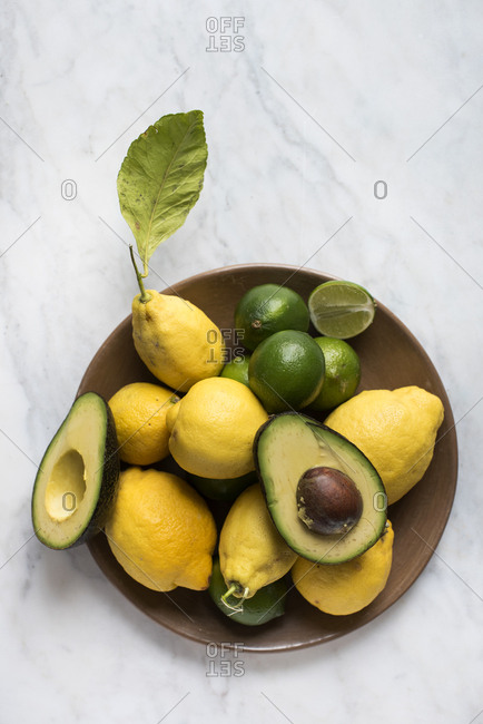 Avocado on a plate with lemons and limes