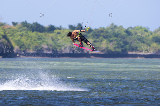Kiteboarder grabbing board in the air