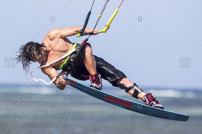 Young man kiteboarding grabbing board in the air