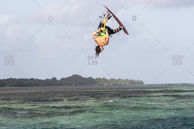 Young man doing kiteboarding tick in midair