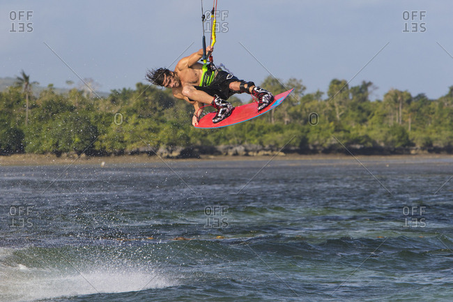 Young man kiteboarding above the waves