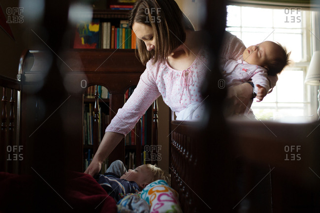 Mother holding baby and checking on toddler in crib