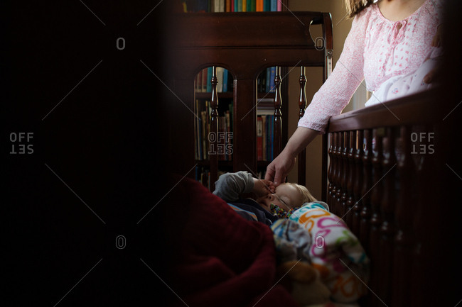 Mother checking on toddler in crib
