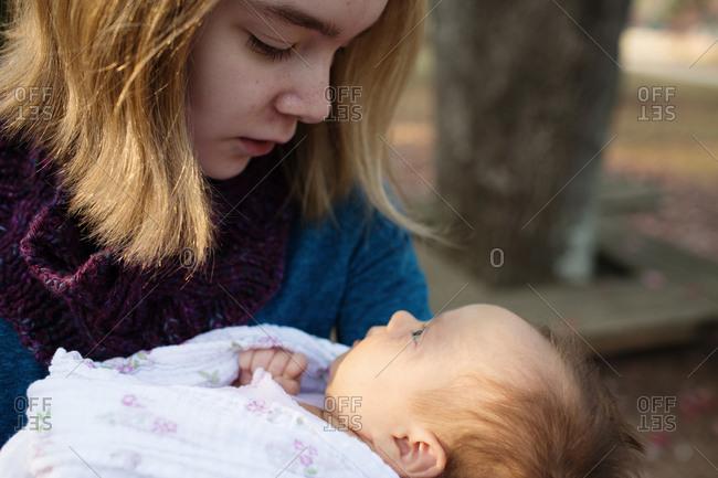 Teen girl gazing at baby