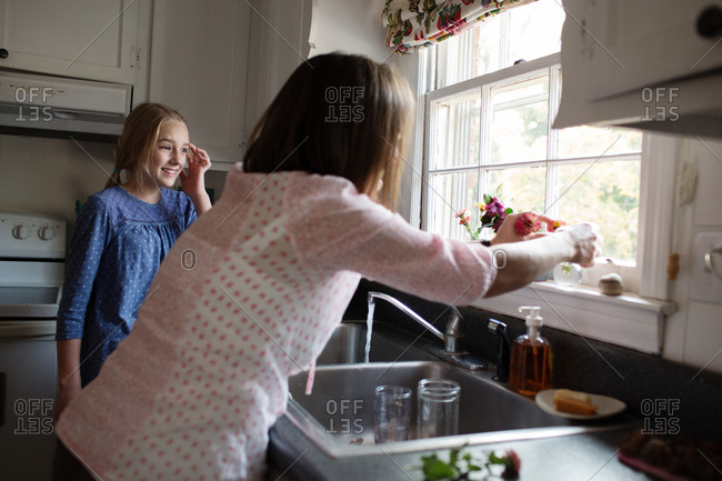Woman placing flowers on windowsill in her kitchen
