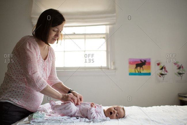 Mother changing newborn baby's clothes