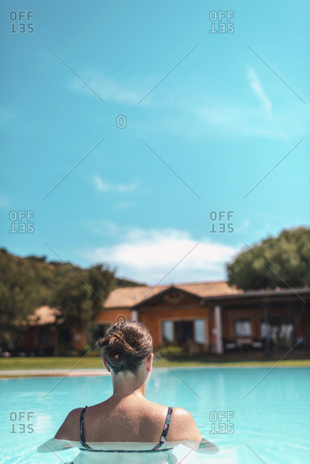 Rear view of woman in clear blue pool