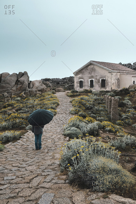 Woman with umbrella walking on stone path by old house