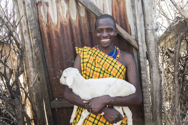 Smiling Maasai villager holding a baby goat at Maasai Mara in Kenya