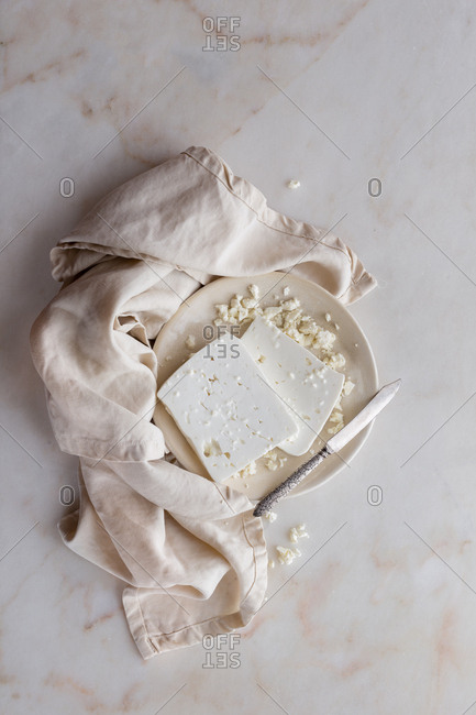Fresh feta cheese on marble backdrop with a linen