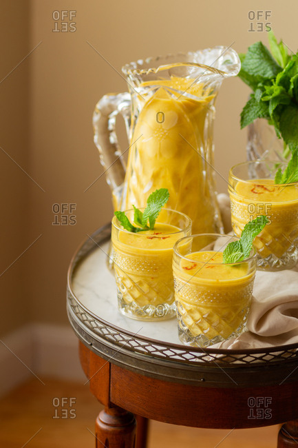 Mango Lassi made with kefir, rum, mango, saffron and cardamom, garnished with mint