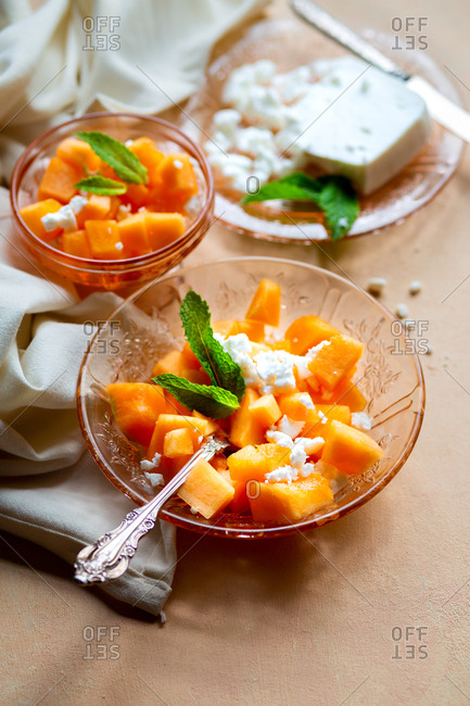 Fresh cantaloupe, fresh feta and fresh mint served on pink depression glass with white linen napkin and vintage silver forks