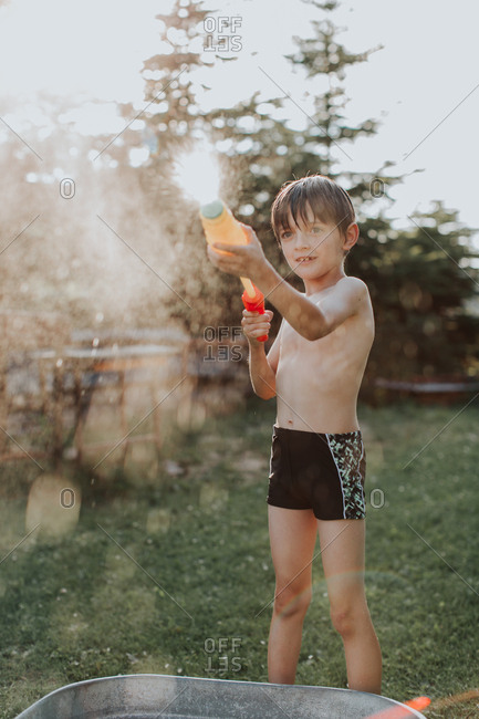 A portrait of a child wearing swimwear playing with a water gun on a hot summer day. A boy spraying water from a water pistol in a garden at summertime.