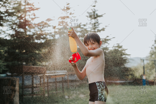 A portrait of an excited child spraying water all over himself on a hot summer day. A happy boy splashing with a water gun in a garden in the summertime.