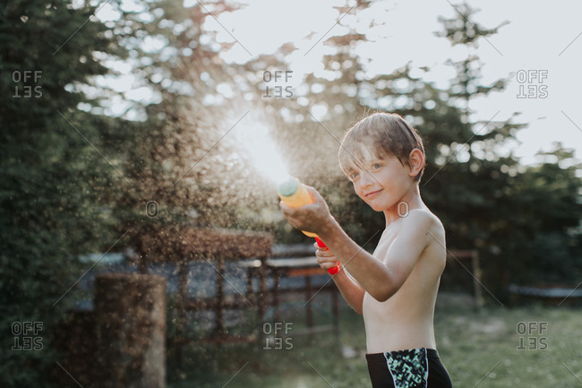 A portrait of a happy child spraying water all over on a hot summer day. A boy wearing swimming trunks playing with a water gun.