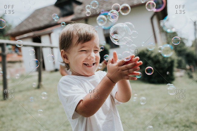 A happy child popping soap bubbles. A portrait of an excited toddler popping soap bubbles outside in a garden on a summer day.