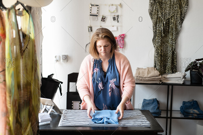 Woman folding clothes in a working in clothing boutique