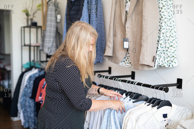 Blonde woman arranging clothes on hangers in a boutique