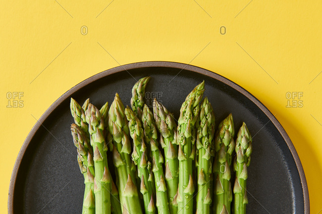 Fresh raw asparagus on black plate on yellow background