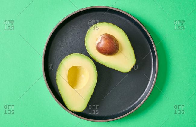 Fresh raw avocado  cut in half on black plate on green background