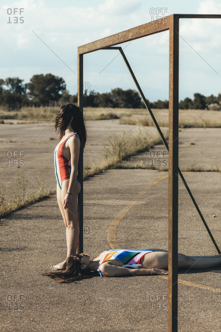 Two women in swimsuits posing with soccer goal on abandoned sports field