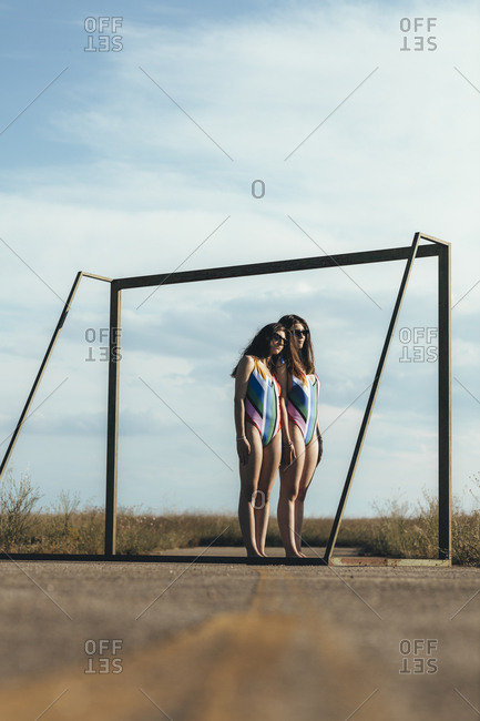 Low angle view of women in swim wear standing together framed by soccer goal on abandoned sports field