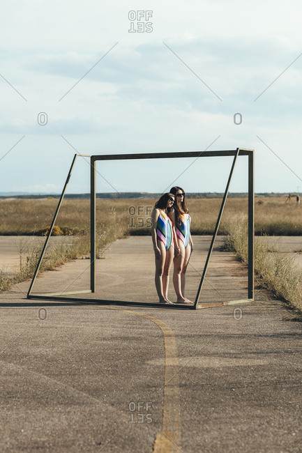 Two women wearing swimsuits standing together in soccer goal on abandoned sports field