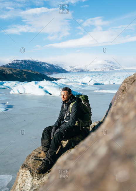 Male backpacker resting on rocks in Iceland