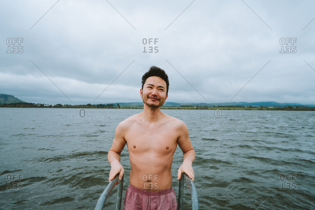 Male tourist getting ready for cold water swim in Scotland lake