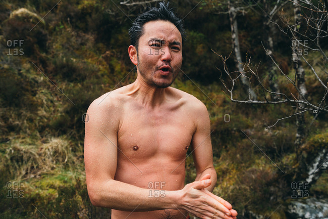 Shirtless man with pained facial expression after icy swim in Scotland