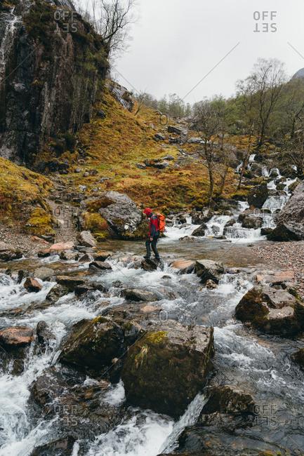 Lone backpacker crossing swift Scottish stream