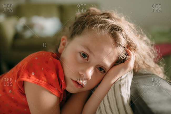 Portrait of young blonde girl sitting alone in living room