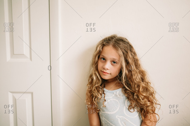 Young girl with long curly blonde hair smirking against wall