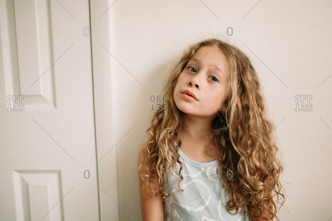 Portrait of blonde girl standing alone against wall