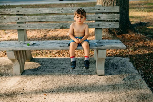 Somber toddler sitting alone on park bench