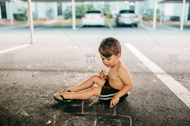 Shirtless toddler playing with chalk in parking space