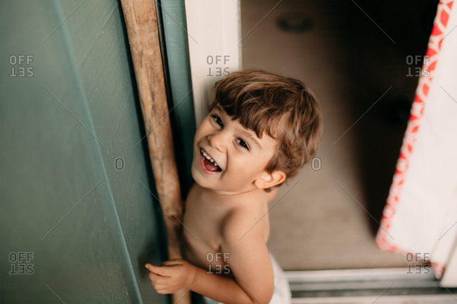 High angle view of small toddler in diaper standing in patio corner