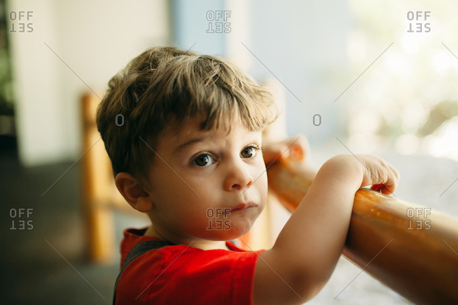 Portrait of serious toddler standing at wooden railing