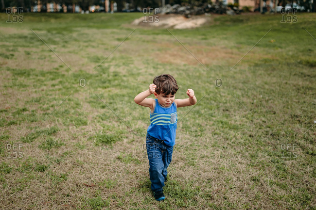 Upset toddler boy stomping through grassy field with fists clenched