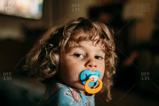Curly haired toddler with pacifier