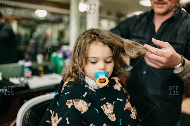 Nervous toddler with pacifier waiting for first haircut
