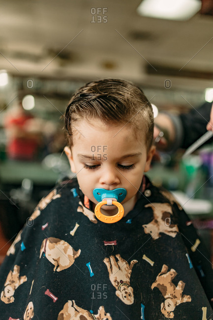 Portrait of young boy's first haircut at the barbershop