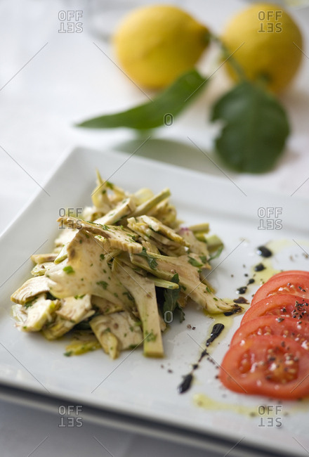 High angle view of artichoke and tomato salad on square plate