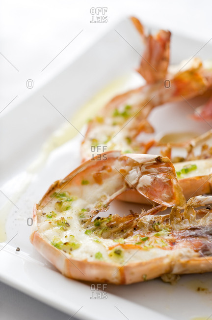 Close up view of grilled langoustines served on square plate