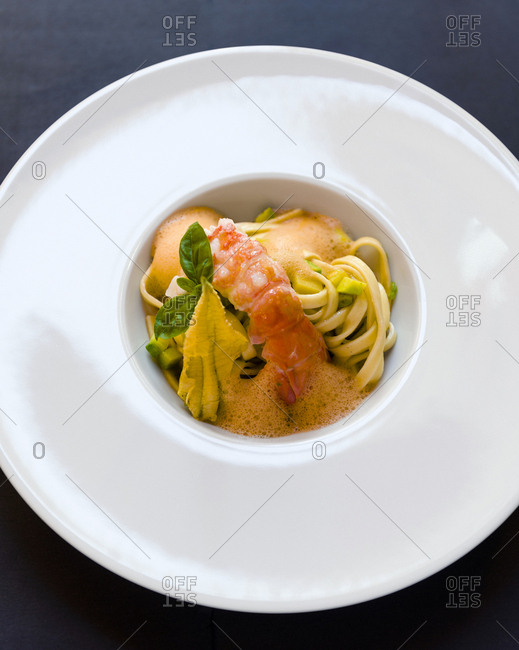 Bowl of fettuccine gamberoni served with a zucchini flower